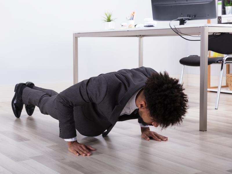 Jeune homme d'affaires fait des push-ups au bureau