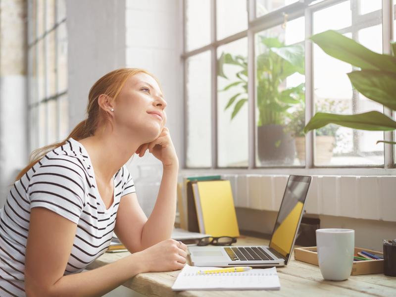 Jeune femme au travail regarde par la fenêtre