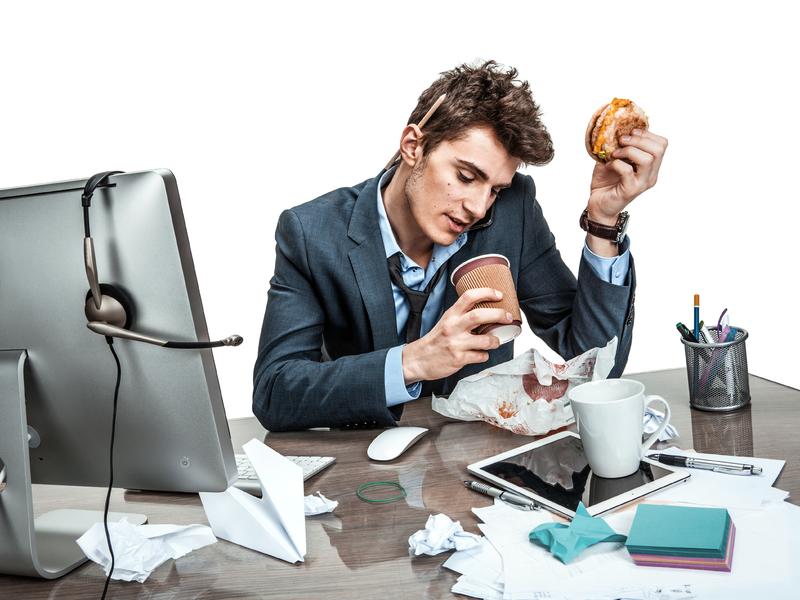 Homme mange à son bureau