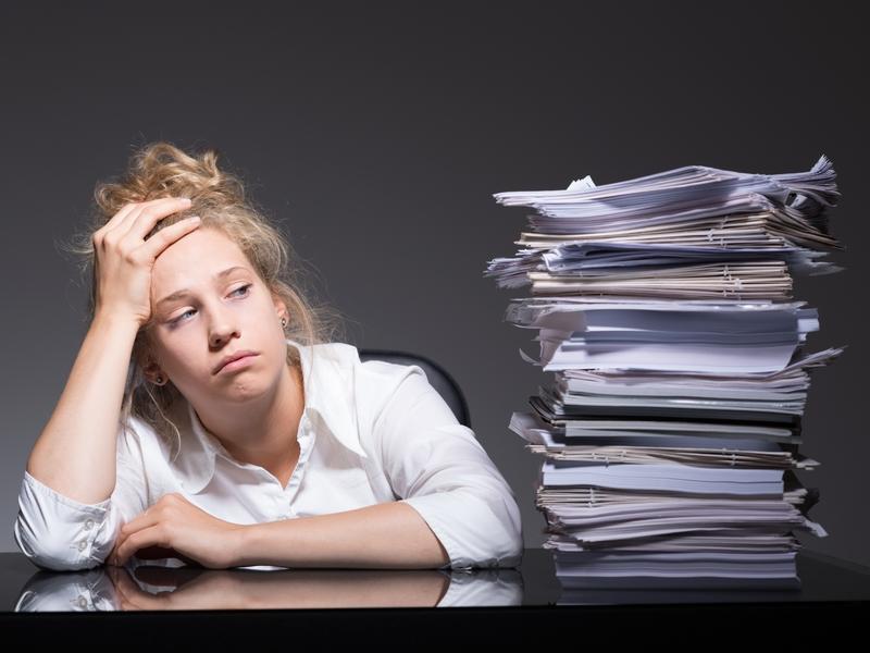 Une femme épuisée regarde une montagne de papiers