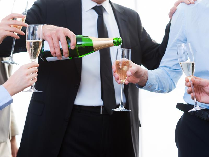 Un cadre sert le champagne à son équipe