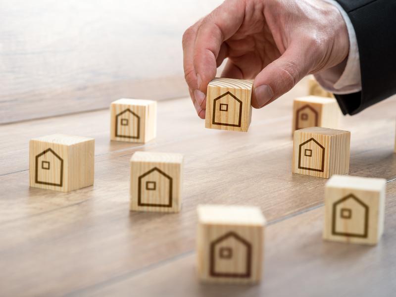 Homme d'affaires jouent avec des blocs de bois avec image de maison