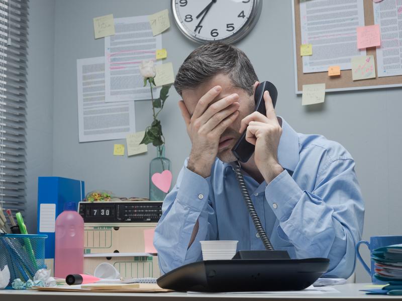 Homme stressé parle au téléphone du bureau