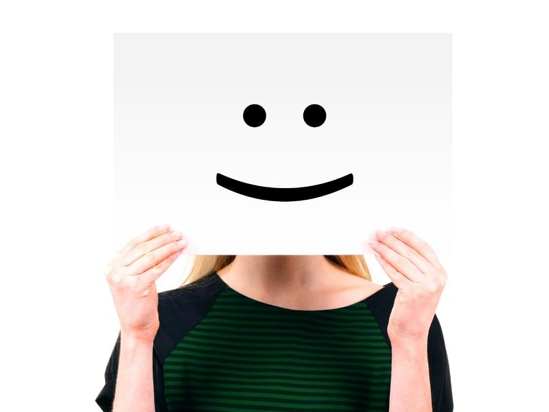 Femme cachée derrière un papier avec un sourire