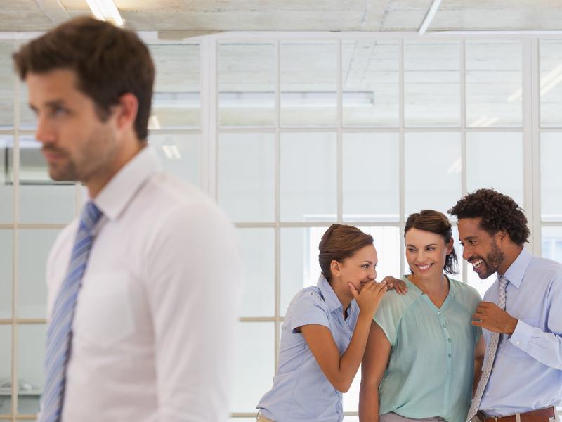 Collègues bavardant derrière le dos d'un jeune employé