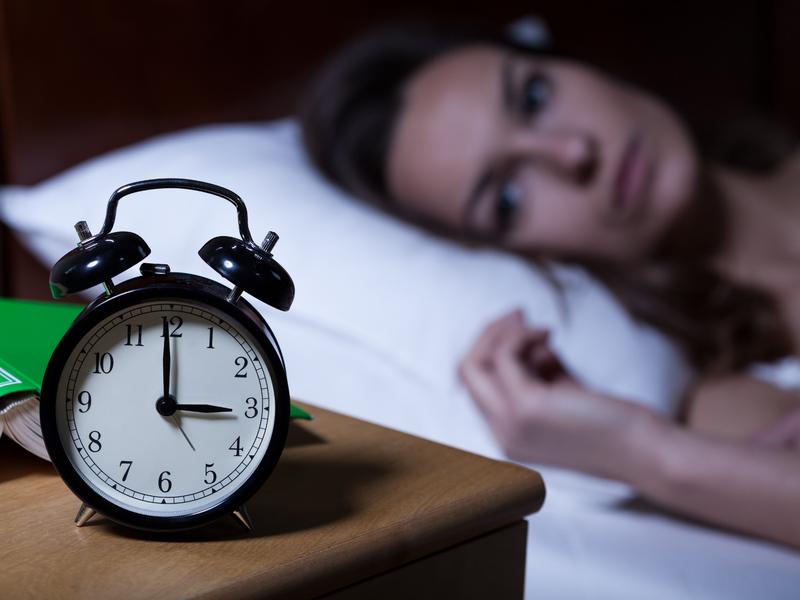 Femme qui ne dort pas avec un horloge à 3h du matin