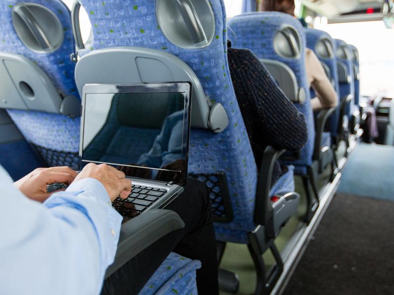 Homme travaille sur son ordinateur assis dans un bus