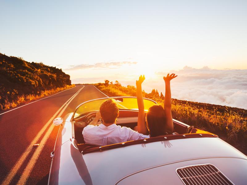 Homme et femme dans une voiture décapotable au soleil