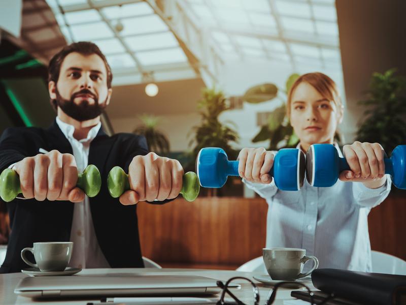 Deux collègues lèvent des poids au bureau