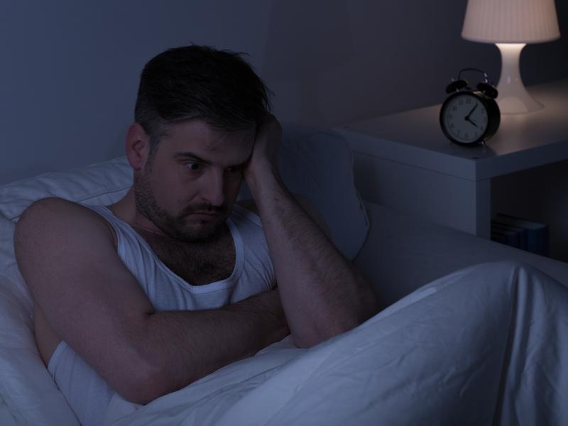 Homme stressé qui n'arrive pas à dormir