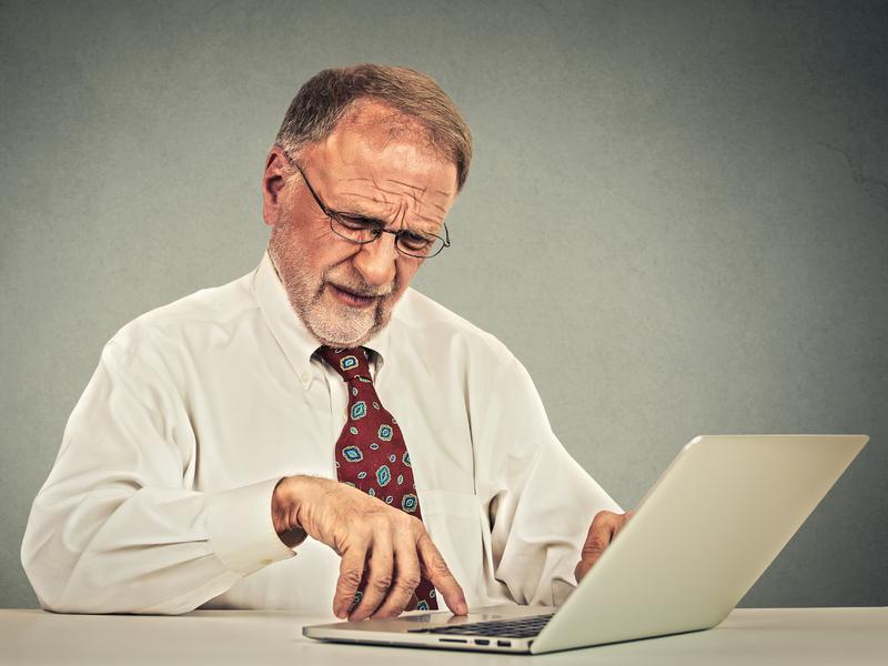 Homme âgé travaille sur ordinateur