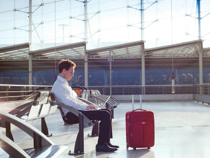 Homme travaille sur son ordinateur portable en attendant son avion dans un aéroport