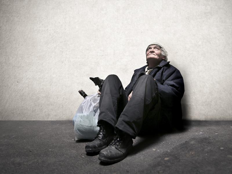 Personne âgée sans abris assise