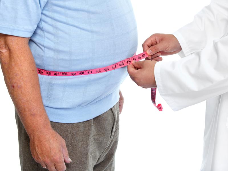 Un médecine mesure la taille d'un homme obèse