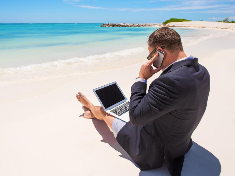 Homme en complet travaille sur la plage