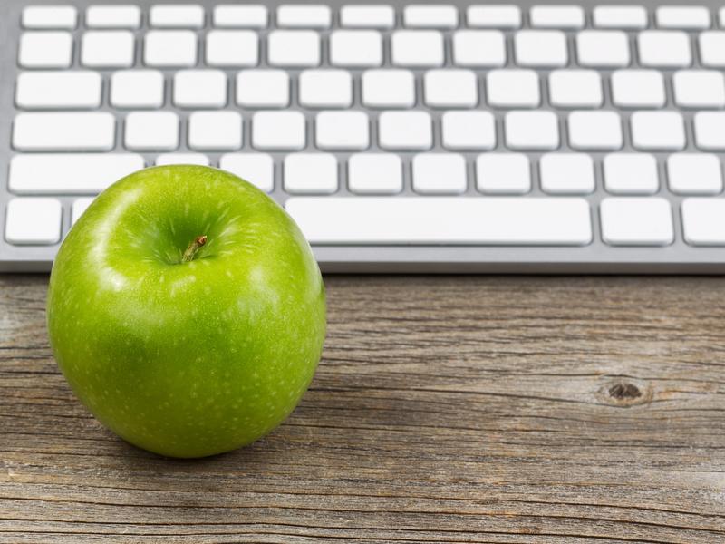 Une pomme devant un clavier d'ordinateur