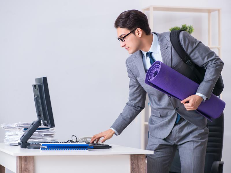 Jeune travailleur avec tapis de yoga devant son ordinateur