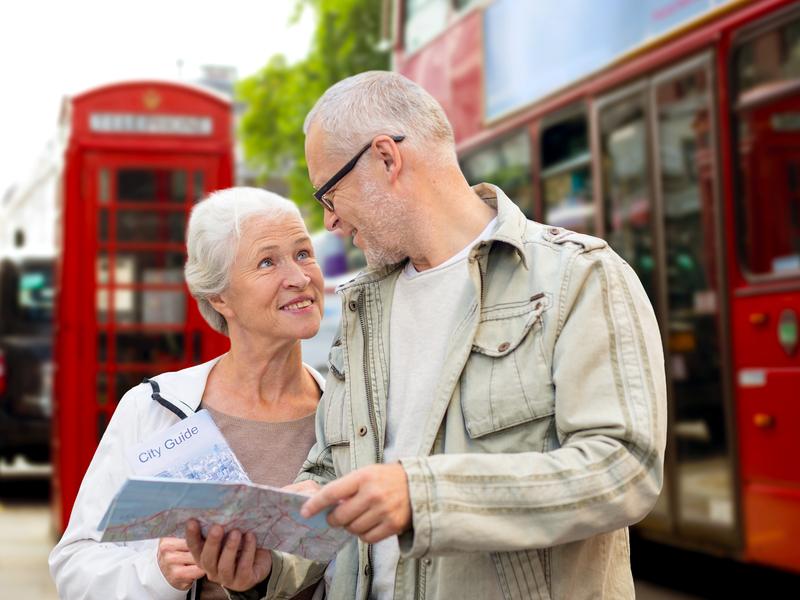 Un couple en vacances à Londres devant un bus rouge et une boite postale