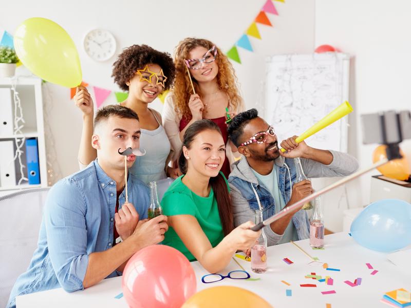 Des collègues font un egoportrait lors d'un party de bureau