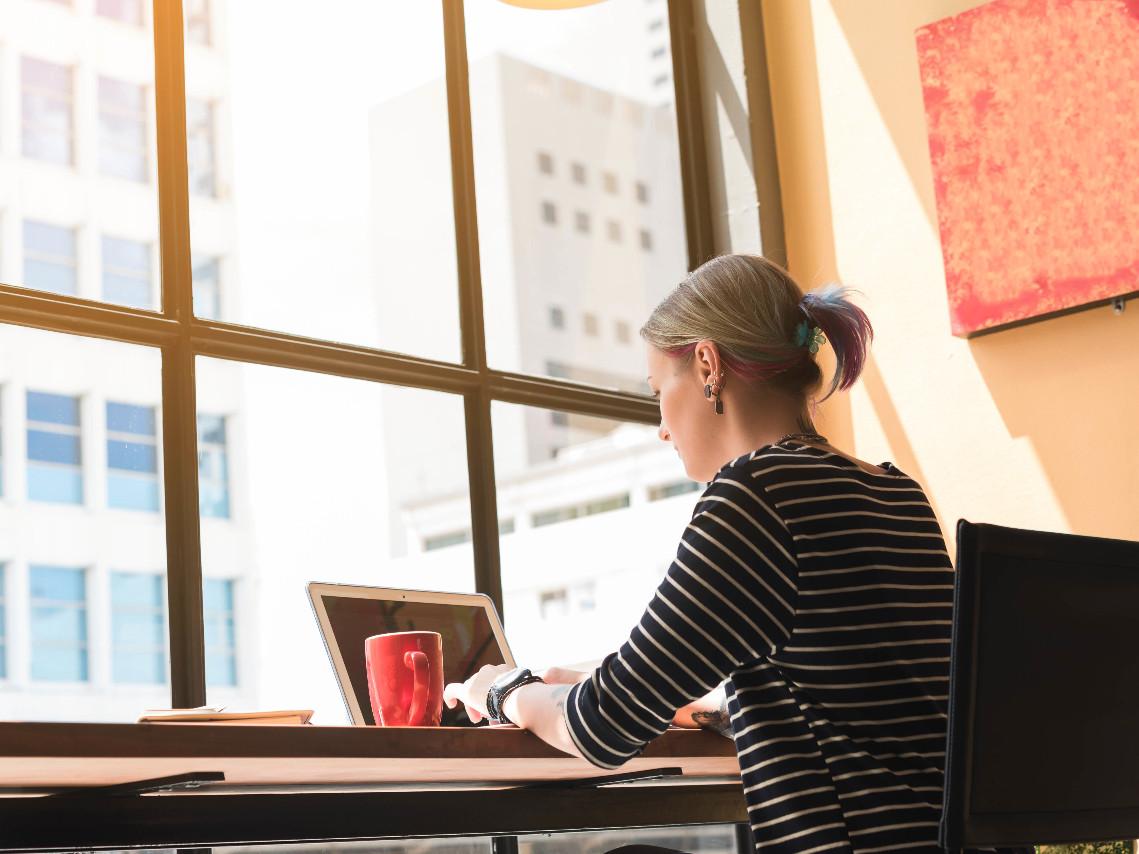 Une pigiste travaille sur son ordinateur dans un café