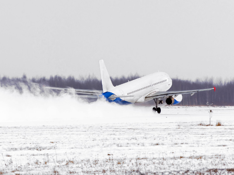 Un avion décolle d'une piste enneigée