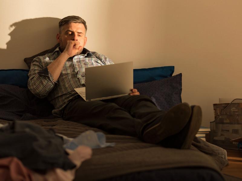 Un homme travaille sur son lit
